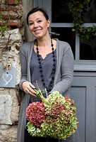 ROQUELIN, LOIRE VALLEY, FRANCE: OWNER ALINE CHASSINE WITH HYDRANGEAS OUTSIDE THE FRONT DOOR OF THE FARMHOUSE